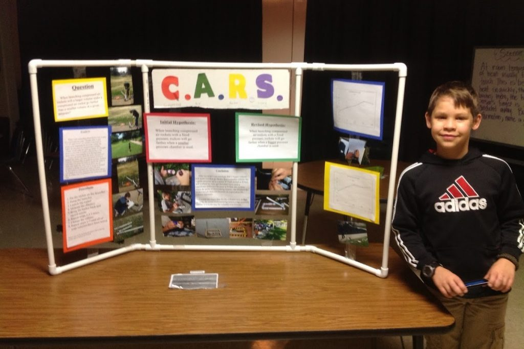Boy stands next to science fair display - made of PVC pipe
