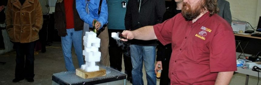 Group watch a man play jenga with tongs and dry ice over an empty aquarium