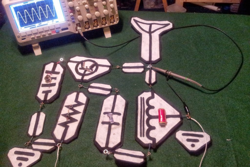 Felt circuit schematic symbols on in the form of a radio circuit connected to oscilloscope showing generated 1Mhz waveform