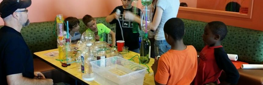 kids making heron fountains out of 2 liter bottles