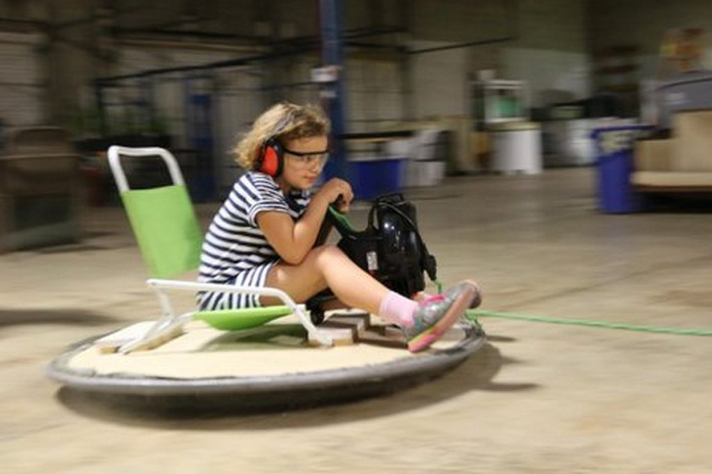 Girl on riding hover board sitting lawn chair holding leaf blow down with speed motion blur
