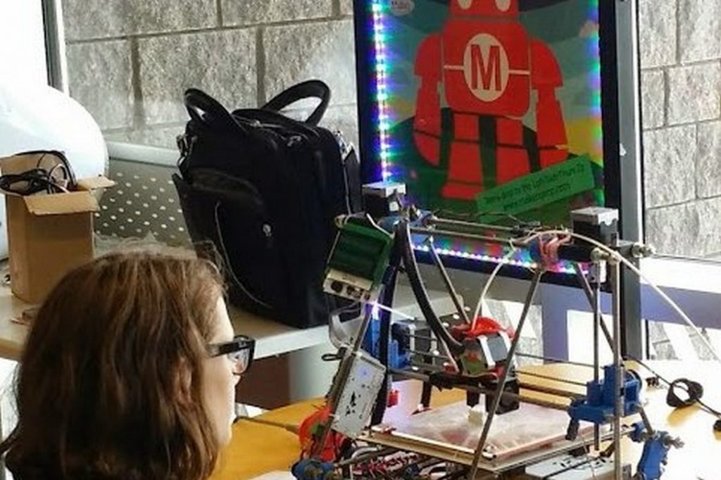 Child sits watching 3D printer in the Library