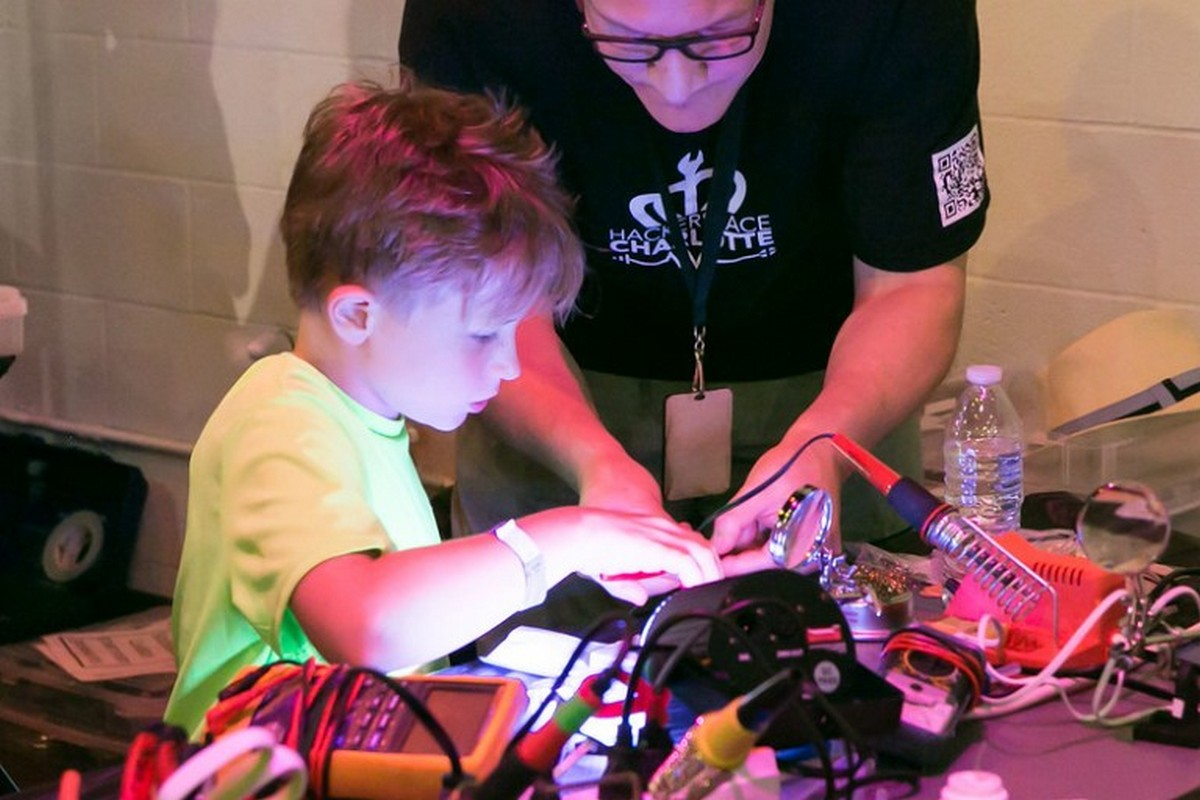 Child sitting at a soldering station with adult looking on