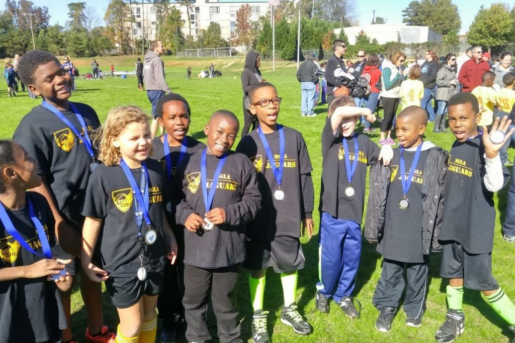 Elementary school kids wearing rugby tournament medals