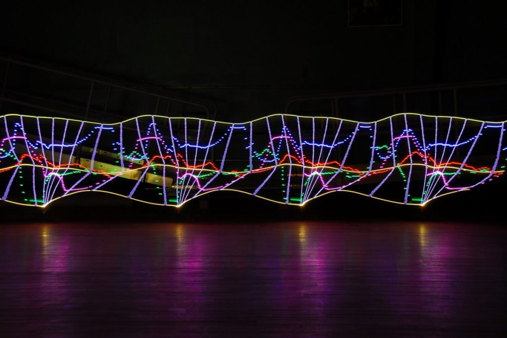 multi colored lights in a dark room as if plotted on a graph...but as a long exposure photo