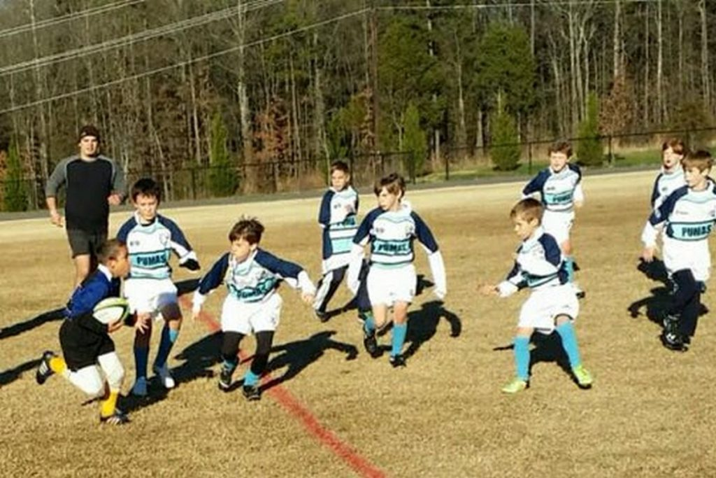 One elementary school rugby player against and entire team.